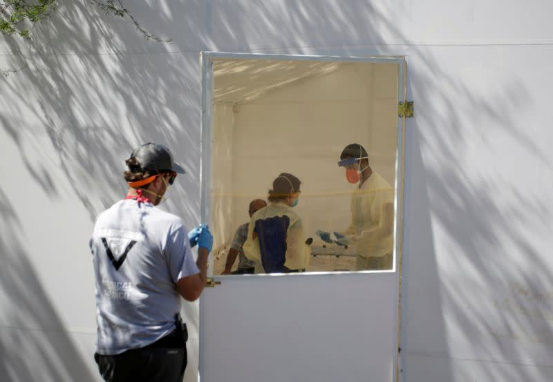 FILE PHOTO: Medical staff from Global Response Management takes samples from a patient suspected of contracting coronavirus disease (COVID-19) at an isolation area of a hospital installed at a migrant encampment in Matamoros