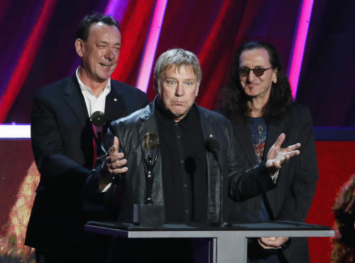 Alex Lifeson, center, Neil Peart, left, and Geddy Lee, of Rush accept their band's induction into the Rock and Roll Hall of Fame during the Rock and Roll Hall of Fame Induction Ceremony at the Nokia Theatre on Thursday, April 18, 2013 in Los Angeles. (Photo by Danny Moloshok/Invision/AP)