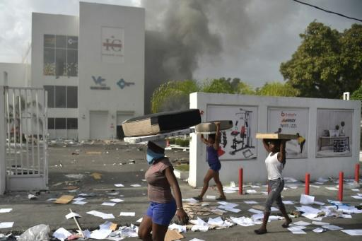 People carry loot from a shop in the commune of Petionville during protests against an increase in fuel prices, which the government has suspended