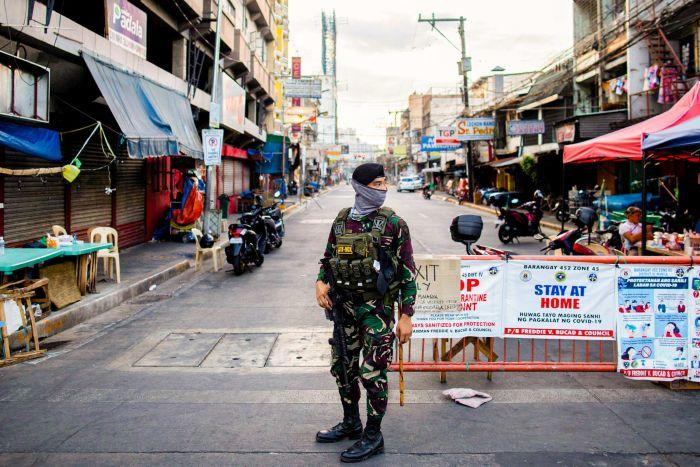 A soldier stands at a road block in Manila in a face mask