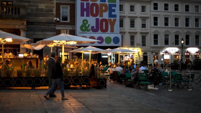 Orang-orang makan dan minum di Covent Garden, di London, Selasa (22/9/2020). Perdana Menteri Inggris, Boris Johnson, telah mengumumkan bahwa pub dan restoran tutup pada pukul 10 malam, karena lonjakan kasus virus corona di seluruh Inggris. (AP Photo / Alberto Pezzali)