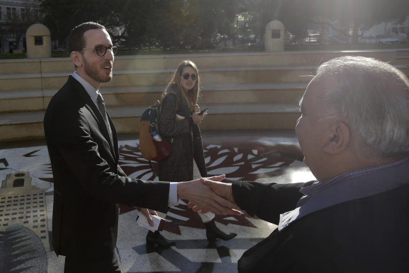 California Sen. Scott Wiener, left, shakes hands with a man after a rally outside of City Hall in Oakland, Calif., Tuesday, Jan. 7, 2020. Wiener announced amendments to a closely-watched bill that would allow more housing to be built near public transportation. (AP Photo/Jeff Chiu)