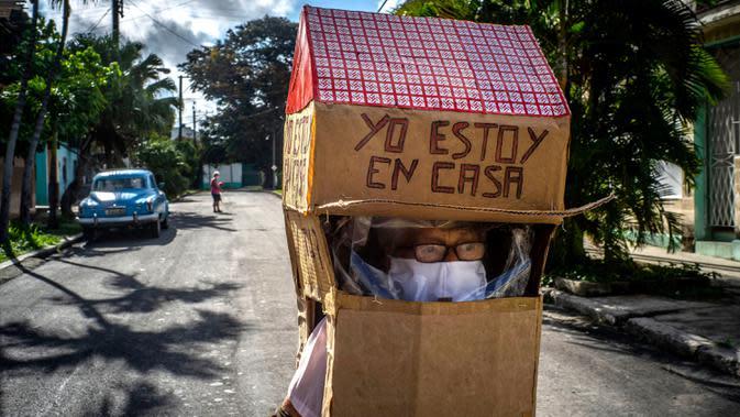 Feridia Rojas, seorang pensiunan perawat (82), memakai kotak kardus berbentuk rumah untuk melindungi dirinya dari penyebaran Covid-19 di Havana, Kuba, 8 Juli 2020. Pakaian pelindung kardus itu dipakai Rojas untuk melakukan aktivitas di luar rumah sehari-hari seperti berbelanja. (AP/Ramon Espinosa)