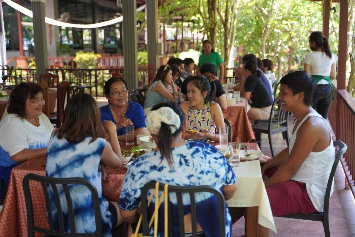 A group of women and men sit at tables in a restaurant surrounded by trees as waitresses walk nearby
