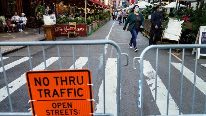 Sebuah gerbang menutup restoran yang mengoperasikan area luar ruangan (outdoor) hingga ke trotoar dan jalanan di New York pada 3 Oktober 2020. Kota tersebut mengizinkan restoran membuat area makan outdoor sebagai upaya mengatasi dampak ekonomi COVID-19 yang berkelanjutan. (AP Photo/John Minchillo)