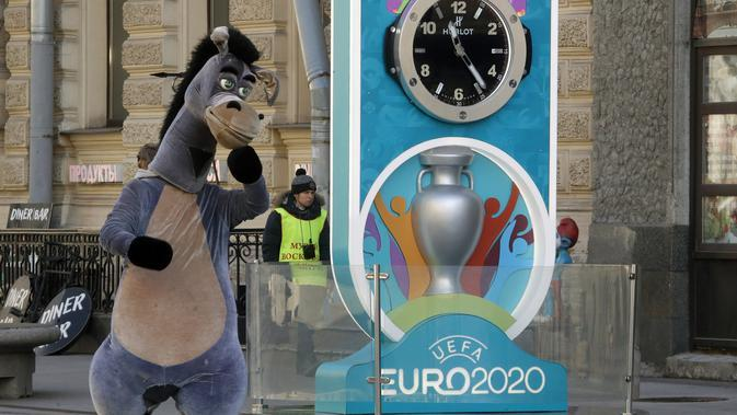 PIALA EROPA 2020 DITUNDA: Seorang penampil berkostum kuda berjalan dekat layar hitung mundur Piala Eropa 2020 di St. Petersburg, Rusia, Selasa (17/3/2020). UEFA resmi menunda Piala Eropa 2020 hingga tahun depan. (AP Photo/Dmitri Lovetsky)