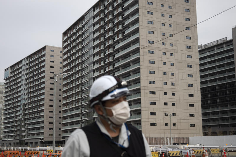 FILE - In this Monday, March 23, 2020, file photo, a masked worker walks through the athletes' village for the Tokyo 2020 Olympics, in Tokyo. The Tokyo Olympics have been moved to next year. The sprawling site on Tokyo Bay - 5,632 apartments - will be sold off after the Olympics. Reports say about one-quarter of the units have already been sold. (AP Photo/Jae C. Hong, File)