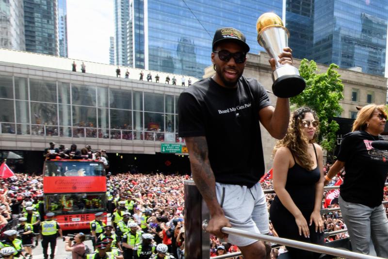 NBA Finals MVP Kawhi Leonard raises the trophy on top of the bus during the Toronto Raptors Championship parade. Source: Getty