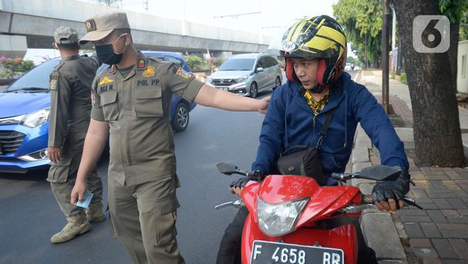 Petugas Satpol PP memberhentikan pengendara motor di Lebak Bulus, Jakarta, senin (14/09/2020). Pemerintah Provinsi DKI Jakarta memperketat kembali PSBB karena kasus Covid-19 terus mengalami peningkatan. (merdeka.com/Dwi Narwoko)