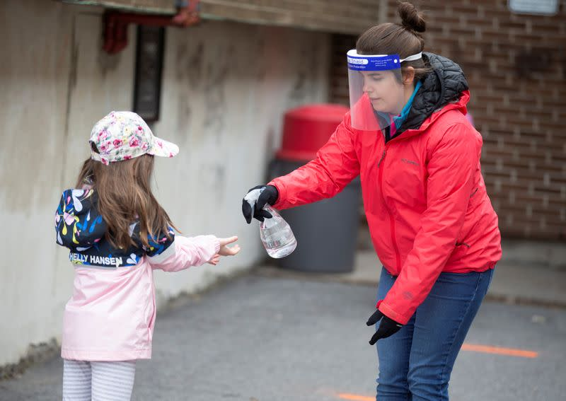 A student has hands sanitized in the schoolyard as schools reopen outside the greater Montreal region in Saint-Jean-sur-Richelieu