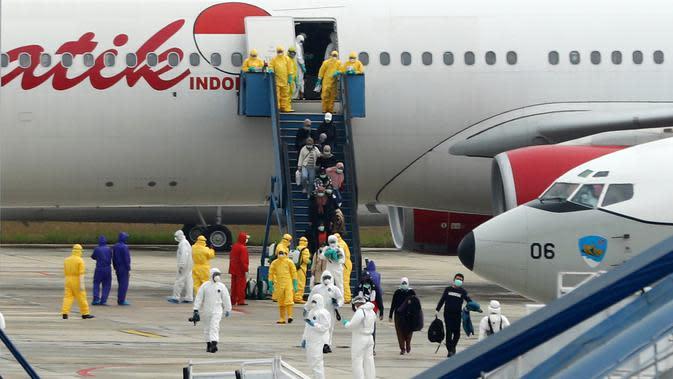 Sejumlah Warga Negara Indonesia (WNI) yang dievakuasi dari Wuhan, China keluar dari pesawat Batik Air di bandara internasional Hang Nadim, Batam, Minggu (2/2/2020). Sebanyak 245 WNI di Wuhan akan dievakuasi ke Indonesia terkait merebaknya virus corona di kota tersebut. (AFP/Ricky Prakoso)