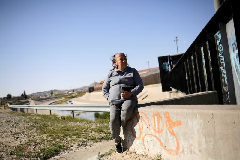 Guadalupe sits near the border fence between Mexico and U.S. where her son was shot in Ciudad Juarez