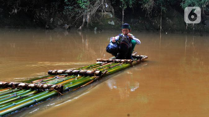 Seorang anak menyeberangi Sungai Cikaniki dengan rakit di Rumpin, Bogor, Jawa Barat, Rabu (15/1/2020). Akibat banjir bandang merobohkan jembatan yang menghubungkan Desa Tonjong Rumpin dan Desa Kantalarang Leuwiliang, warga terpaksa memanfaatkan perahu rakit untuk melintas. (merdeka.com/Arie Basuki)