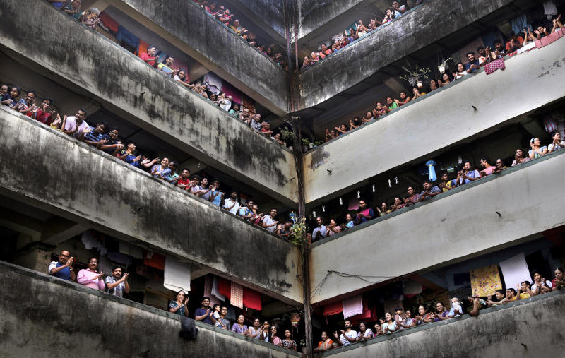 """People clap from balconies in show of appreciation to health care workers at a Chawl in Mumbai, India, Sunday, March 22, 2020. India is Sunday observing a 14-hour """"people's curfew"""" called by Prime Minister Narendra Modi in order to stem the rising coronavirus caseload in the country of 1.3 billion For most people, the new coronavirus causes only mild or moderate symptoms. For some it can cause more severe illness. (AP Photo/Rafiq Maqbool)"""