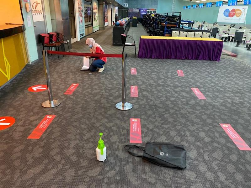 An employee puts up signs to guide customers on social distancing at Sunway Mega Lanes in preparation for reopening of the bowling centre in Subang Jaya. — Picture courtesy of Sunway Mega Lanes