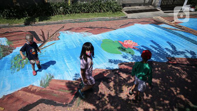 Anak-anak melintas di atas jalan yang telah dilukis mural di Jalan Keuangan, Cilandak, Jakarta, Rabu (26/8/2020). Mural di sepanjang jalan Keuangan menuju museum Basoeki Abdullah itu bertujuan memperindah wilayah tersebut serta sebagai ajang promosi museum. (Liputan6.com/Faizal Fanani)