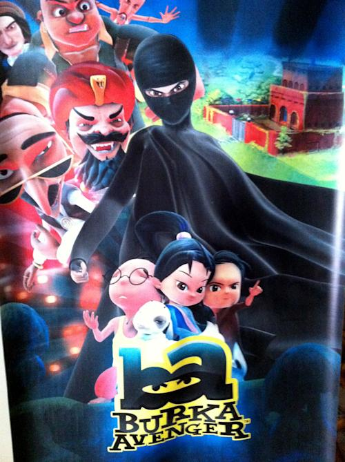 """This Thursday, July 11, 2013 photo shows a poster for the """"Burka Avenger"""" cartoon series, which is scheduled to start running on Geo TV in early August. Wonder Woman and Supergirl now have a Pakistani counterpart in the pantheon of female superheroes _ one who shows a lot less skin. Meet Burka Avenger: a mild-mannered teacher with secret martial arts skills who uses a flowing black burka to hide her identity as she fights local thugs seeking to shut down the girls' school where she works. Sadly, it's a battle Pakistanis are all too familiar with in the real world.(AP Photo/Sebastian Abbot)"""