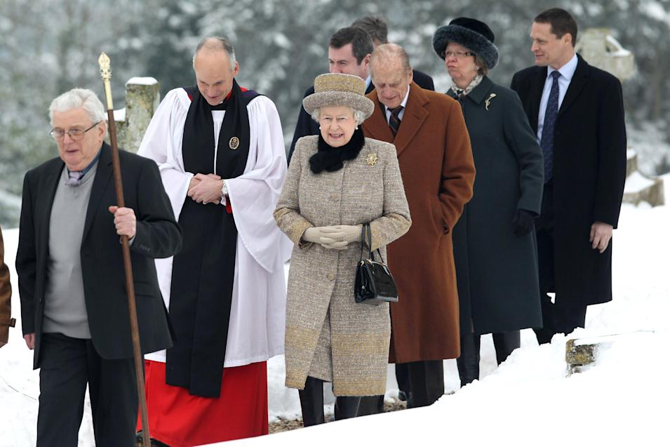 Britain's Queen Elizabeth II, centre, and her husband Prince Philip, Duke of Edinburgh, 3rd right, accompanied by an unidentified member of the clergy , 2nd left, arrive with others at the church of St Peter and St Paul at West Newton, eastern England, Sunday Feb. 5, 2012. The queen braved the cold and snow to attend church Sunday on the eve of her Diamond Jubilee anniversary. The 85-year-old monarch marks 60 years on the throne on Monday. The anniversary will be marked by a series of regional, national and international events throughout 2012.  Elizabeth ascended the throne when her father, George VI, died on Feb. 6, 1952. She is the longest-serving monarch after Queen Victoria, who reigned for more than 63 years. (AP Photo/PA, Chris Jackson) UNITED KINGDOM OUT  NO SALES  NO ARCHIVE