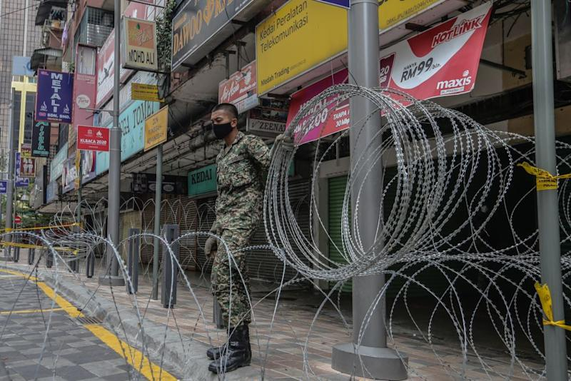 An Armed Forces personnel cordons off the vicinity of Selangor Mansion, on Jalan Masjid India, with barbed wire on April 7, 2020. — Picture by Firdaus Latif