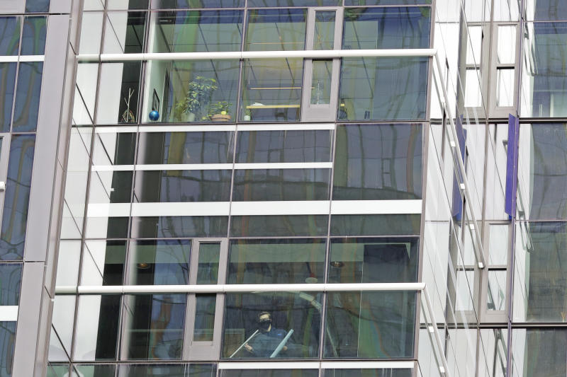 A worker cleans a window in an Amazon.com office building, Thursday, April 30, 2020, in downtown Seattle. Amazon is expected to announce earnings for the first quarter of 2020 at the close of markets Thursday, a report that is expected to be closely watched due to the effects of the coronavirus outbreak on the company. (AP Photo/Ted S. Warren)