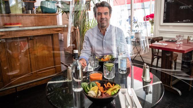 Christophe Gernigon berpose di bawah penemuannya, purwarupa gelembung plexiglass Plex'Eat di restoran H.A.N.D di Paris, Prancis, pada 27 Mei 2020. Plex'Eat yang dapat melindungi dari virus corona Covid-19 ini mudah dipasang dan dilepas, mudah dibersihkan dan didisinfeksi. (Xinhua/Aurelien Morissard)