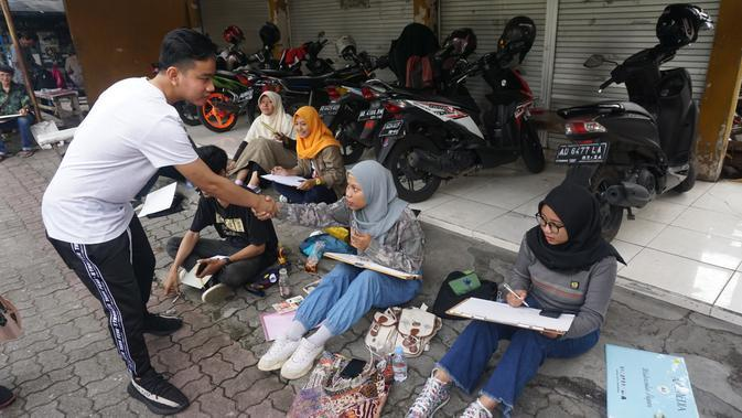 Gibran Rakabuming Raka saat menyalami para pelukis yang berkumpul di kawasan Pujasari, Sriwedari, Solo, Selasa (14/1).(Liputan6.com/Fajar Abrori)