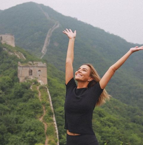A photo of The Bachelor Australia star Kristen Czyszek wearing a black t-shirt on the Great Wall of China in China.
