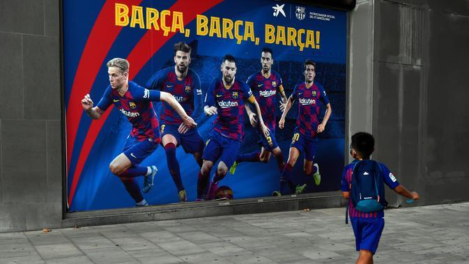 Seorang bocah melewati poster bergambar Messi dan pemain Barcelona lainnya (AFP)