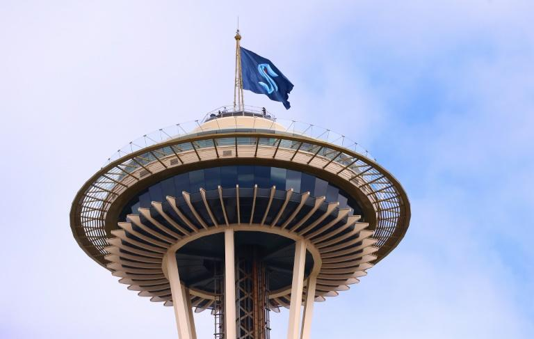 A flag displaying the logo of the Seattle Kraken, the 2021-22 NHL expansion team  nickname that was unveiled Thursday, flies atop Seattle's iconic Space Needle