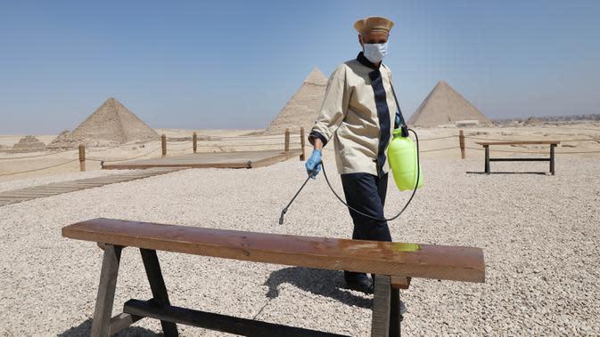 Pekerja menyemprotkan disinfektan di dekat Piramida Giza di Giza, 25 Agustus 2020. Mesir telah menerima 126.000 wisatawan sejak negara itu membuka kembali resor tepi lautnya untuk penerbangan internasional dan turis mancanegara pada 1 Juli, setelah ditutup akibat COVID-19. (Xinhua/Ahmed Gomaa)