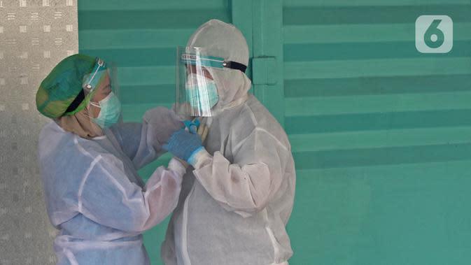 Tenaga kesehatan mengenakan alat pelindung diri (APD) sebelum melakukan tes swab di GSI Lab (Genomik Solidaritas Indonesia Laboratorium), Jakarta, Sabtu (3/10/2020). Pemerintah telah menyepakati batas maksimal harga tes usap atau swab mandiri sebesar Rp900 ribu. (Liputan6.com/Herman Zakharia)