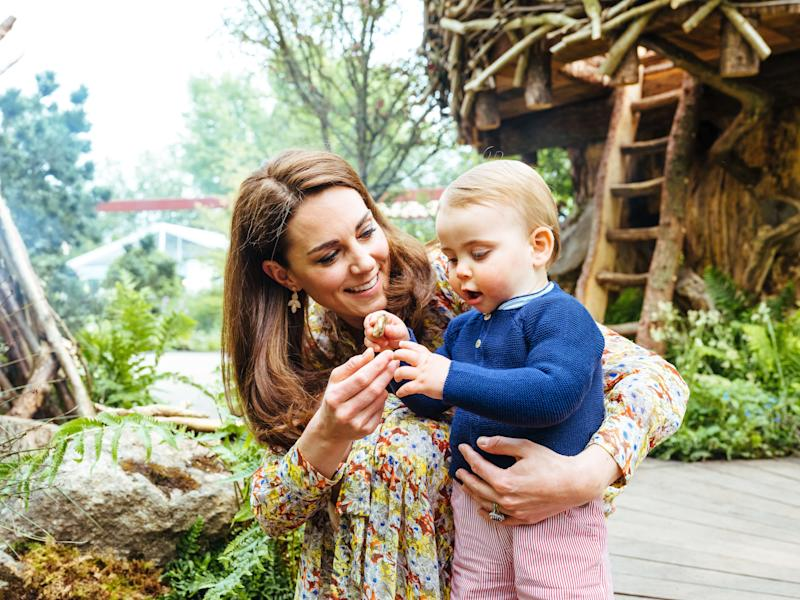 Kate holds Louis as he holds a pebble from the garden [Photo: Matt Porteous]