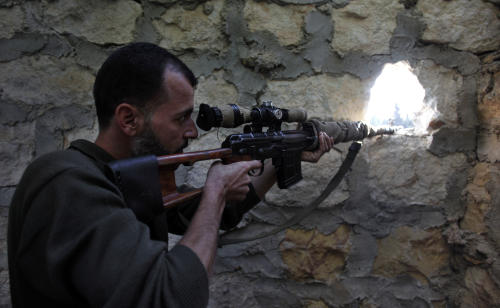 In this Wednesday, Nov. 14, 2012 file photo, a rebel sniper aims at a Syrian army position on the outskirts of Aleppo, Syria. Through mid-2012, rebel power grew and Assad's army ramped up its response. Relentless government shelling leveled neighborhoods and killed hundreds. Regular reports emerged of mass killings by the regime or thugs loyal to it, pushing more Syrians toward armed struggle. The government, which considers the opposition terrorist gangs backed by foreign powers, denied any role, and does not respond to requests for comment on its military. The rebels, too, were accused of atrocities. (AP Photo/ Khalil Hamra, File)