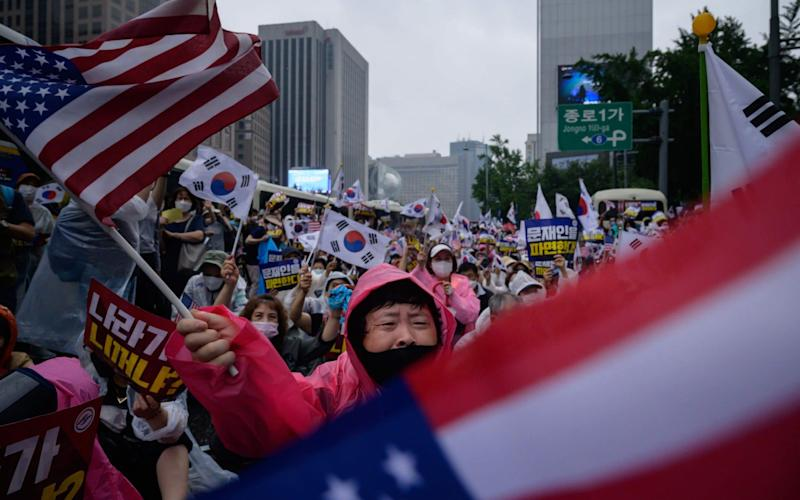 Members of pro-US conservative right-wing and religious christian groups wave flags and shout slogans during an anti-government rally in the central Gwanghwamun area of Seoul - ED JONES/AFP