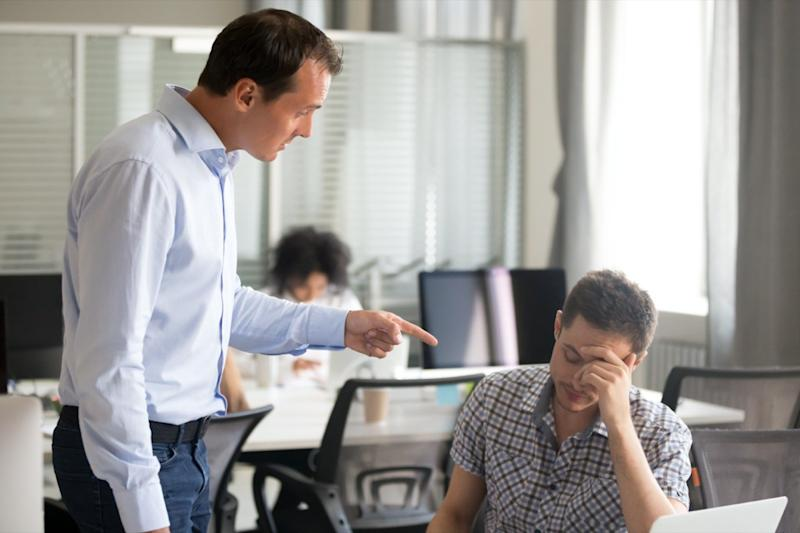 middle aged white male boss yelling and pointing at employee