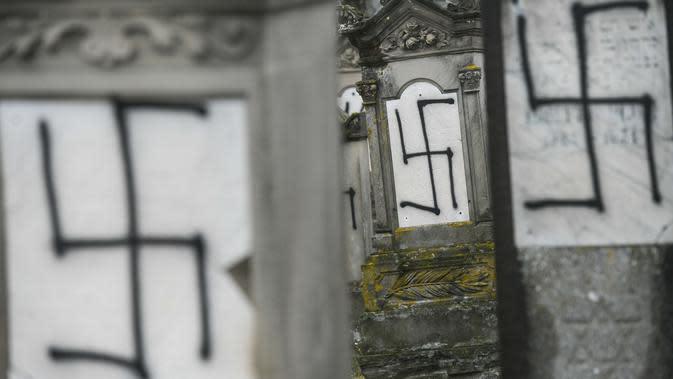 Sejumlah batu nisan dan monumen Holocaust yang dicoret-coret dengan simbol swastika nazi di sebuah pemakaman Yahudi di Strasbourg, Prancis (17/12). Aksi vandalisme ini diketahui dilakukan Selasa di pemakaman Yahudi Herrlisheim. (AFP Photo/Sebastien Bozon)