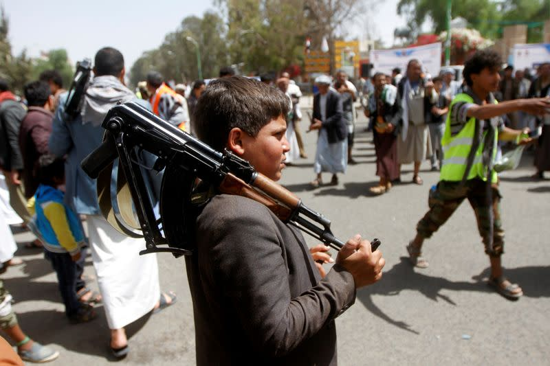 FILE PHOTO: A boy carries a weapon as he and Houthi supporters are seen during a gathering in Sanaa