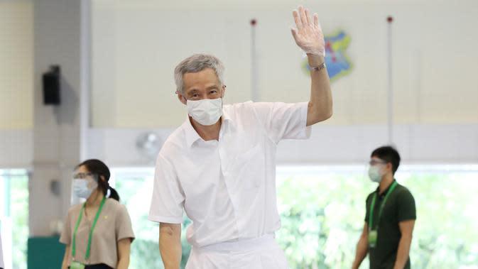 PM Lee Hsien Loong melambai saat memberikan suara dalam pemilu di TPS Sekolah Dasar Alexandra, Singapura, Jumat (10/7/2020). Pemilu di tengah pandemi COVID-19, warga Singapura memberikan suara dengan mengenakan masker dan sarung tangan plastik. (Ministry of Communications and Information via AP)