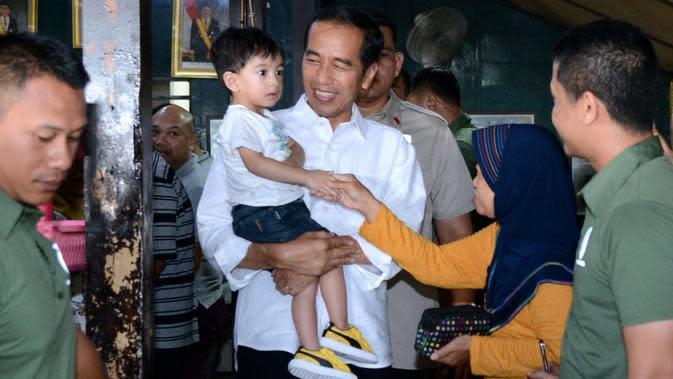 Presiden Jokowi mengajak sang cucu, Jan Ethes makan soto di Pasar Kliwon, Solo, Jumat (30/3). Presiden datang didampingi Ibu Negara Iriana juga putra pertamanya Gibran Rakabuming serta istrinya Selvi Ananda. (Liputan6.com/Pool/Kris-Biro Pers Setpres)