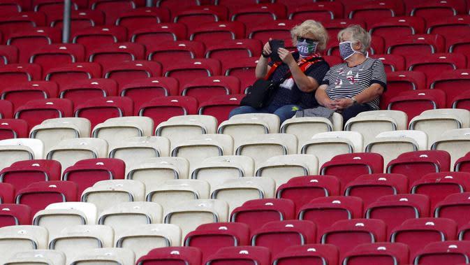 Dua orang penonton saat menyaksikan pertandingan antara VfB Stuttgart melawan SC Freiburg pada laga Bundesliga, Sabtu (19/9/2020). Sejumlah liga di Eropa telah mengijinkan fans menonton langsung pertandingan di stadion. (AP Photo/Matthias Schrader)