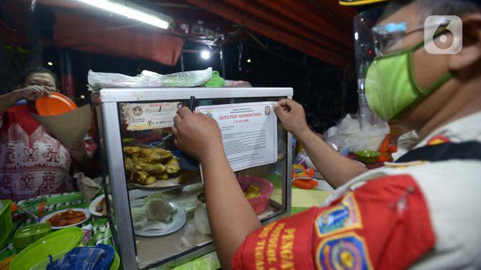 Petugas Satpol PP menempelkan stiker penutupan sementara tempat makan saat penertiban penerapan PSBB di wilayah Kecamatan Pulogadung, Jakarta, Jumat (18/9/2020). Malam, Razia dilakukan memastikan ketidakadaannya konsumen makan ditempat tersebut. (merdeka.com/Imam Buhori)