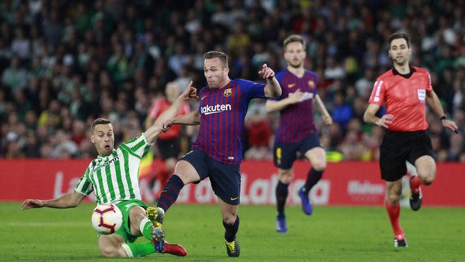 Gelandang Barcelona, Arthur Melo, berusaha melewati pemain Real Betis, Tello, pada laga La Liga 2019 di Stadion Benito Villamarin, Minggu (17/3). Barcelona menang 4-1 atas Real Betis. (AP/Miguel Morenatti)