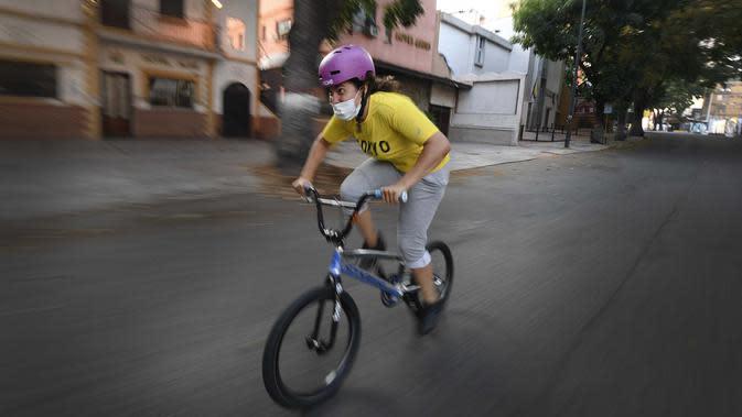 Atlet BMX asal Venezuela, Stefany Hernandez mengenakan masker saat latihan di Caracas, 25 April 2020. Di tengah karantina wilayah guna mengekang penyebaran Covid-19, peraih medali Olimpiade 2016 itu berlatih tiga kali seminggu untuk meraih tiket tampil di Olimpiade 2021. (AP/Matias Delacroix)