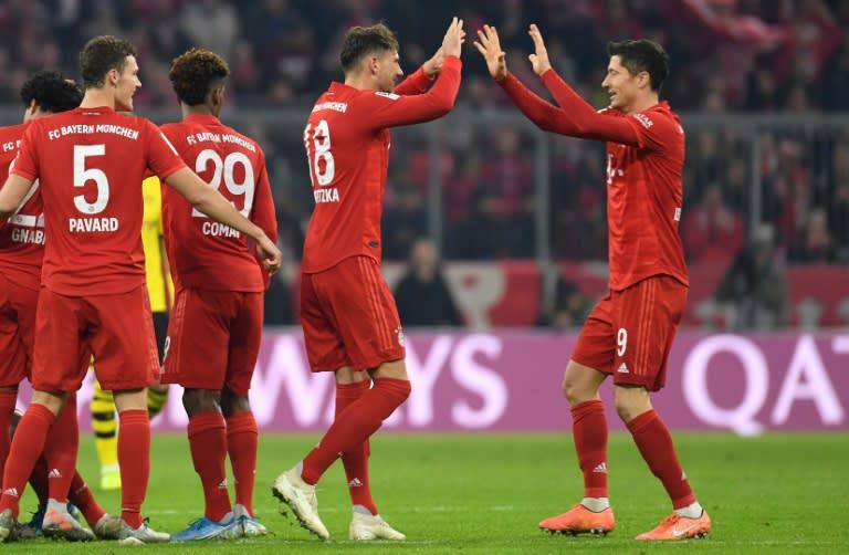 Bayern Munich's Polish striker Robert Lewandowski (R) celebrates with team-mate Leon Goretzka during the rout of Dortmund on Saturday