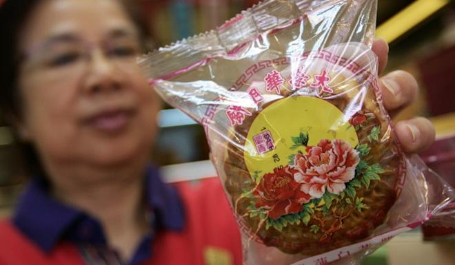 A staff member shows a Wing Wah mooncake in Wan Chai. Photo: Edward Wong