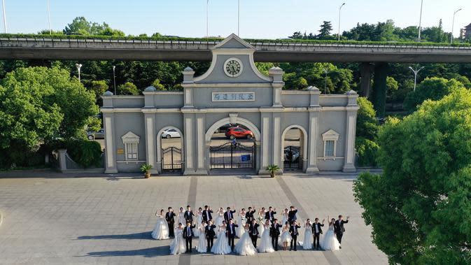 Para pasangan pengantin berpose bersama di Nanjing, Provinsi Jiangsu, China timur, pada 19 Mei 2020. Sebanyak 15 pasangan pengantin pada Selasa (19/5) berfoto bersama di Nanjing menjelang upacara pernikahan massal mereka yang dihelat pada 20 Mei. (Xinhua/Ji Chunpeng)