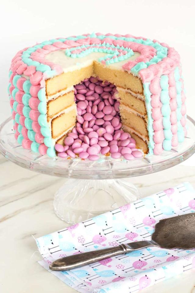 """<p>Make your gender reveal party a little sweeter with a delicious, candy-filled cake! When you cut into the cake, blue or pink M&Ms will spill out to artfully reveal whether you're having a boy or a girl.  </p><p><strong>Get the tutorial at <a href=""""https://www.evolvingtable.com/gender-reveal-cake/"""" target=""""_blank"""">Evolving Table</a>.</strong></p><p><a class=""""body-btn-link"""" href=""""https://www.amazon.com/Ms-Light-White-Chocolate-Candy/dp/B00NZFG9HU/?tag=syn-yahoo-20&ascsubtag=%5Bartid%7C10050.g.30900240%5Bsrc%7Cyahoo-us"""" target=""""_blank"""">SHOP PINK OR BLUE M&MS</a></p>"""
