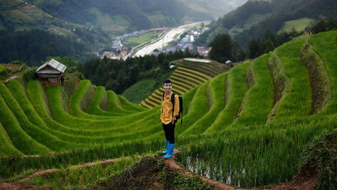 Pengunjung berfoto dengan latar belakang sawah terasering di distrik Mu Cang Chai, Vietnam utara pada 18 September 2020. Pesawahan terasering di Mu Cang Chai merupakan destinasi-destinasi wisata yang atraktif dan menyerap kedatangan banyak wisatawan domestik dan mancanegara. (Manan VATSYAYANA/AFP)