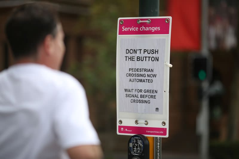 A jogger moves past a sign telling people not to push the crosswalk button in the city centre of Sydney