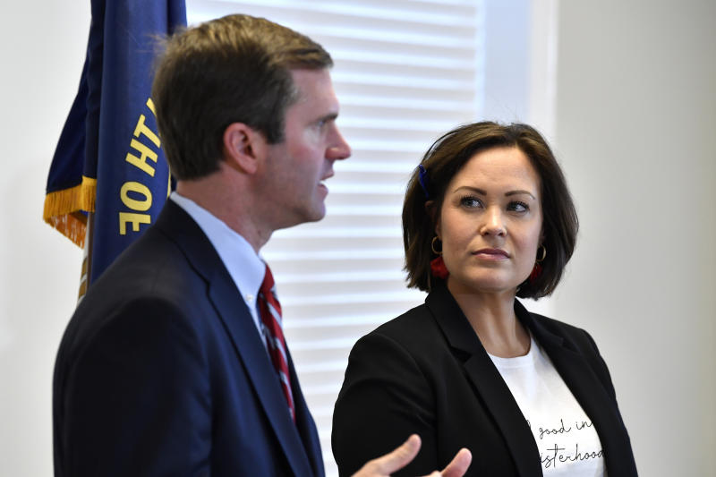 """FILE - In this Nov. 14, 2019, file photo, Kentucky Lt. Gov.-elect Jacqueline Coleman, right, looks on as Gov.-elect Andy Beshear speaks with reporters following the concession of incumbent Governor Matt Bevin in Frankfort, Ky. It's a role that seems scripted for Coleman, as an educator transitioning to the job as a """"full partner"""" in a Democratic administration that vows to make public education a top priority. (AP Photo/Timothy D. Easley, File)"""